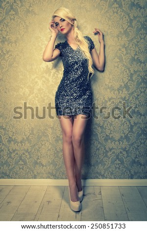 alluring blonde woman in short silver dress - stock photo