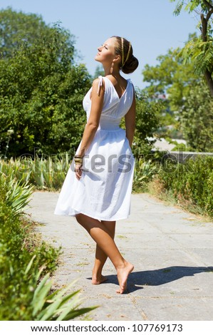 Alluring brown-haired woman outdoors in Greek goddess style in luxury dress standing back. Stylish romantic girl in a white sundress walking in the park. romantic concept. Amazing Nymph. Greece - stock photo