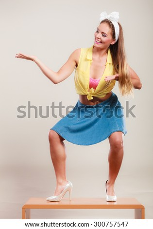 Alluring seductive pretty pin up girl wearing hairband bow, skirt and high heels. Attractive gorgeous young retro woman dancing on table with empty hand palm for copy space. - stock photo