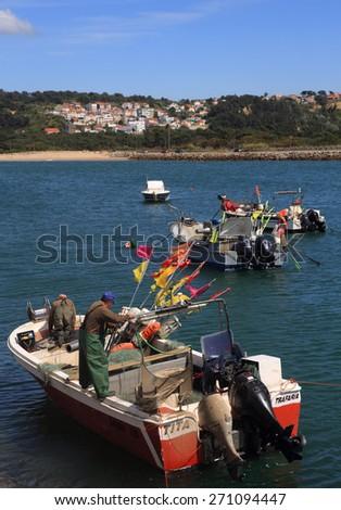 ALMADA, PORTUGAL - APRIL 17: A crew of coastal fishermen prepare their boat for sea in the tiny port of Traferia, on the Tagus River estuary. On April 17 , 2015 in Almada, Portugal. - stock photo