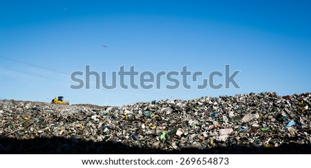 Almada, Portugal 2014: Landfill with bulldozer working, against beautiful blue sky full of sea birds.  - stock photo