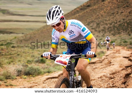 "ALMATY, KAZAKHSTAN - APRIL 30, 2016: G.Torgautov (N23) in action at Adventure mountain bike cross-country competition in mountains ""Jeyran Trophy 2016""  - stock photo"