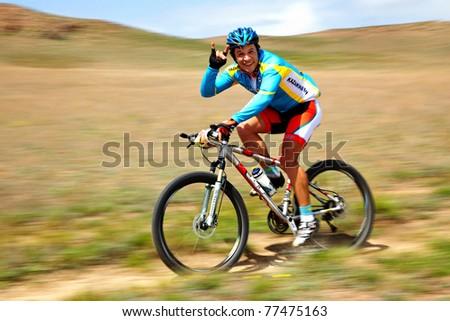 "ALMATY, KAZAKHSTAN - APRIL 30: N.Zaitcev (N2) in action at Adventure mountain bike cross-country marathon in mountains ""Jeyran Trophy 2011"" April 30, 2011 in Almaty, Kazakhstan. - stock photo"