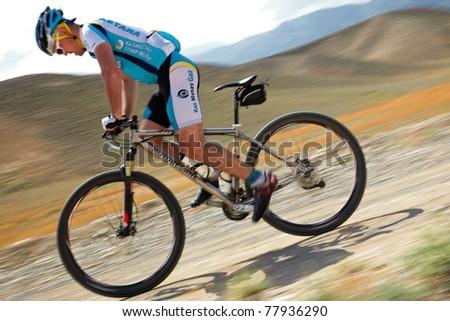 "ALMATY, KAZAKHSTAN - APRIL 30: R.Nurjanov (N24) in action at Adventure mountain bike cross-country marathon in mountains ""Jeyran Trophy 2011"" on April 30, 2011 in Almaty, Kazakhstan. - stock photo"