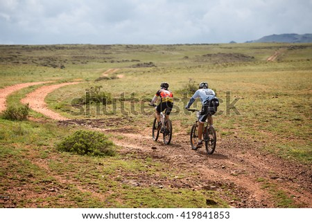 "ALMATY, KAZAKHSTAN - APRIL 30, 2016: Two unknown riders in action at Adventure mountain bike cross-country competition in mountains ""Jeyran Trophy 2016""  - stock photo"