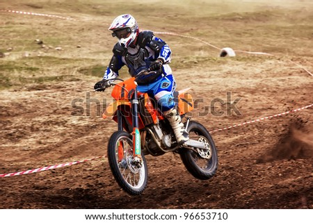 """ALMATY, KAZAKHSTAN - APRIL 10: V.Popov(1) flies through the air at the Motocross competition """"Fabrichny Cup""""- Open Championship of Kazakhstan on April 10, 2011 in Kargaly, Kazakhstan. - stock photo"""