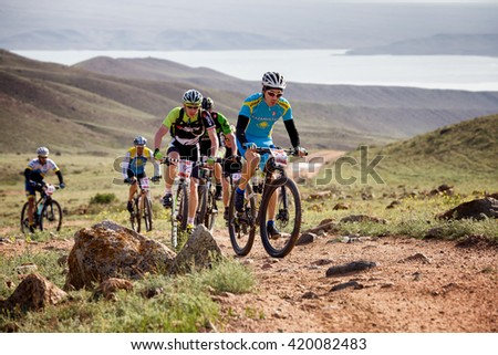 "ALMATY, KAZAKHSTAN - MAY 01, 2016: G.Torgautov (N23) in action at Adventure mountain bike cross-country competition in mountains ""Jeyran Trophy 2016""  - stock photo"