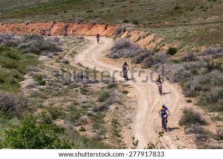 "ALMATY, KAZAKHSTAN - MAY 1, 2015: Group of competitors in action at Adventure mountain bike marathon ""Jeyran Trophy 2015"" - stock photo"