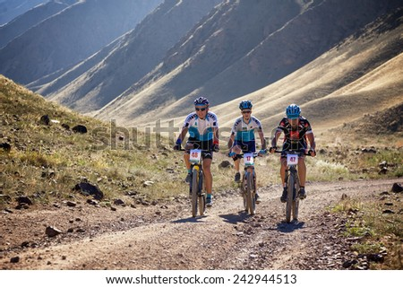"ALMATY, KAZAKHSTAN - SEP 05, 2010: P.Nevdakh (N48) and others in action at Adventure mountain bike cross-country competition in mountains ""Bartogay Marathon 2010""  - stock photo"