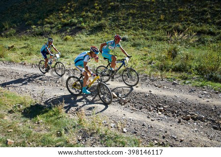 "ALMATY, KAZAKHSTAN - SEPTEMBER 04, 2011: Three unknown competitors in uniform Team Astana  in action at Adventure mountain bike cross-country marathon in mountains ""Marathon Bartogay-Assy-Batan 2011""  - stock photo"