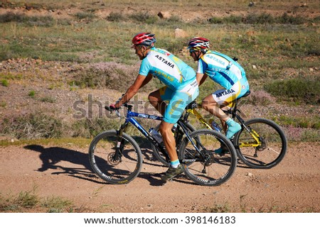 "ALMATY, KAZAKHSTAN - SEPTEMBER 04, 2011: Two unknown competitors in uniform Team Astana  in action at Adventure mountain bike cross-country marathon in mountains ""Marathon Bartogay-Assy-Batan 2011"" - stock photo"