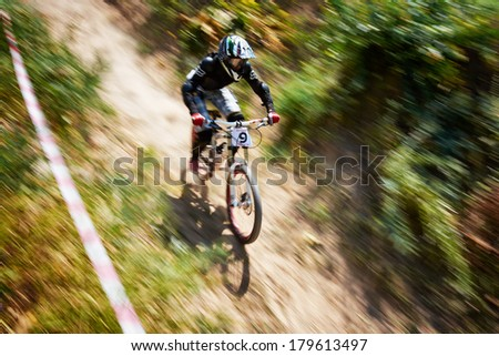 "ALMATY, KAZAKSTAN - AUGUST 03: P.Rezaev (N9) in action at Mountain Bike sports event Superiority of ""Cycling club named A.Vinokurov"" Downhill in Almaty, Kazakstan Aug 03, 2013.  - stock photo"