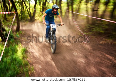 """ALMATY, KAZAKSTAN - AUGUST 03: T.Lunev (N17) in action at Mountain Bike sports event Superiority of """"Cycling club named A.Vinokurov"""" Downhill in Almaty, Kazakstan Aug 03, 2013. - stock photo"""