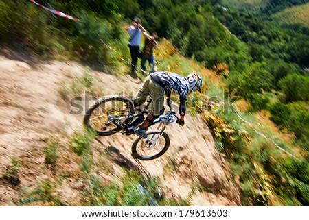 "ALMATY, KAZAKSTAN - AUGUST 03: Unknown rider in action at Mountain Bike sports event Superiority of ""Cycling club named A.Vinokurov"" Downhill in Almaty, Kazakstan Aug 03, 2013.  - stock photo"
