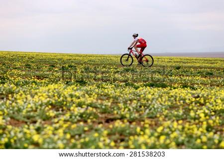 "ALMATY, KAZAKSTAN - MAY 02, 2015: A.Michilov (N2) in action at Adventure mountain bike cross-country marathon in mountains ""Jeyran Trophy 2015""  - stock photo"