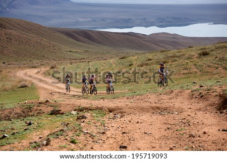 "ALMATY, KAZAKSTAN - MAY 02, 2014: Competitors in action at Adventure mountain bike cross-country marathon in mountains ""Jeyran Trophy 2014""  - stock photo"