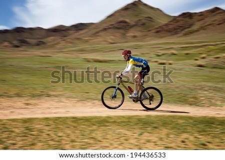 "ALMATY, KAZAKSTAN - MAY 01, 2014: J.Bakytbekuly(N4) in action at Adventure mountain bike cross-country marathon in mountains ""Jeyran Trophy 2014""  - stock photo"