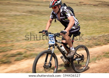 "ALMATY, KAZAKSTAN - MAY 01, 2014: S.Mazurin(N22) in action at Adventure mountain bike cross-country marathon in mountains ""Jeyran Trophy 2014""  - stock photo"