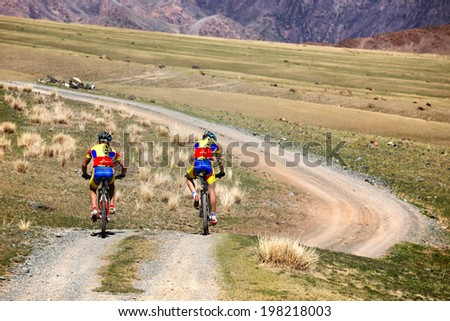 "ALMATY, KAZAKSTAN - MAY 03, 2014: Two bikers in action at Adventure mountain bike cross-country marathon in mountains ""Jeyran Trophy 2014""  - stock photo"