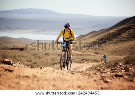 "ALMATY, KAZAKSTAN - SEP 09, 2009: V.Marchenko (N8) in action at Adventure mountain bike cross-country competition in mountains ""Bartogay marathon 2009""  - stock photo"