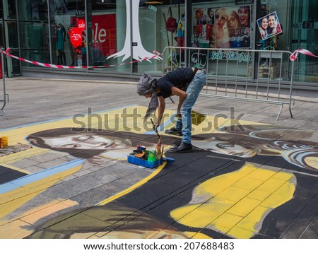 ALMERE, NETHERLANDS - 22 JUNE 2014: Artist at work on a street painting in the streets of the city of Almere - stock photo
