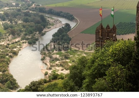 Almodovar Del Rio medieval castle with flags of Spain and Andalusia above Guadalquivir  river - stock photo