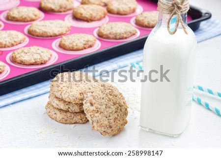 Almond and coconut cookies with a bottle of milk and straws. Cookies in the baking pan in the background. - stock photo