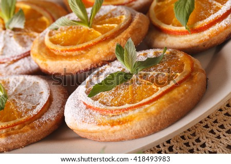 Almond cookies with oranges, decorated with mint macro on a plate. horizontal