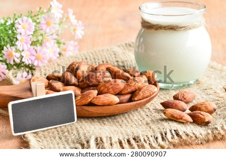 Almond milk in glass with almonds and blank back wooden tag on sack background. - stock photo