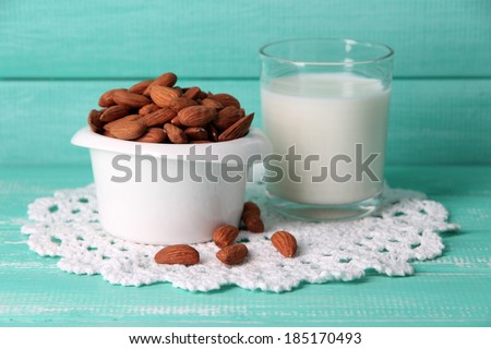 Almond milk in glass with almonds in bowl, on color wooden background - stock photo