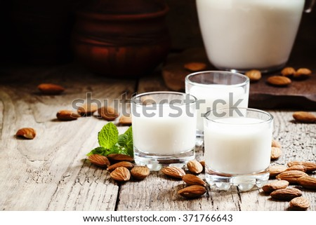 Almond milk in small glasses and spilled dry almonds on old wooden background, selective focus - stock photo