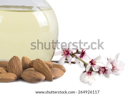 almond oil and almonds with flowers on white background - stock photo