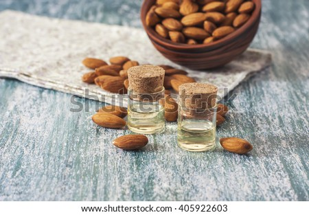Almond oil in bottle  and nuts on wooden background. Selective focus - stock photo