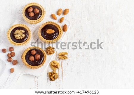 Almond walnut hazelnut chocolate small tarts on a white background, space for text - stock photo