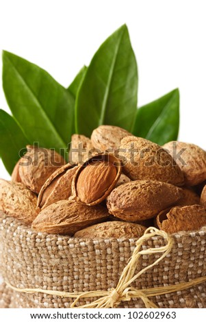 Almond with leaves in a bag on a white background - stock photo
