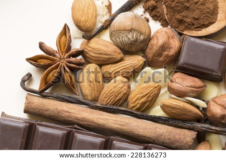 Almonds and hazelnuts with spices and chocolate on a beige ceramic plate - stock photo