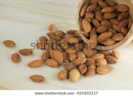 Almonds in a bowl on wooden table. - stock photo