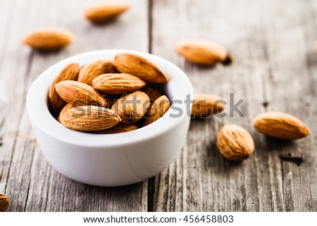 almonds in ceramic bowl on wooden background - stock photo