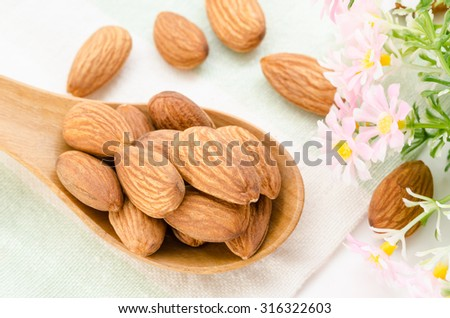 Almonds in wooden spoon with flower on tablecloth background. - stock photo