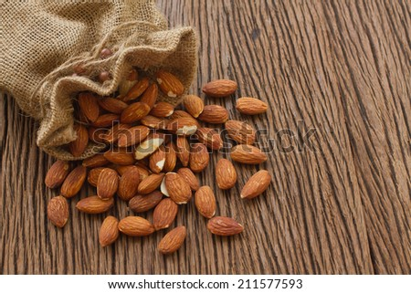 Almonds on wooden background - stock photo