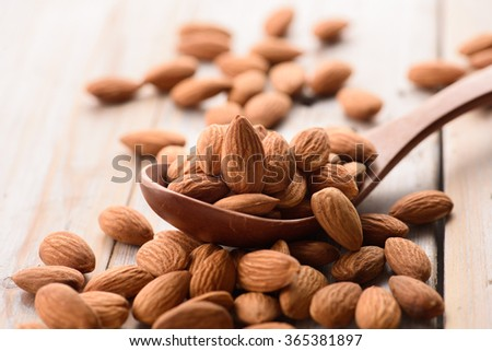 Almonds pour from wood spoon - stock photo