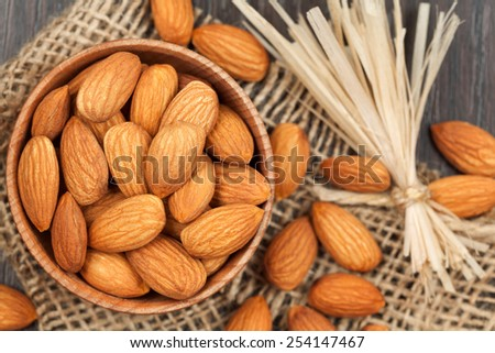 Almonds super food in a wooden dish on vintage textile background with retro toning - stock photo