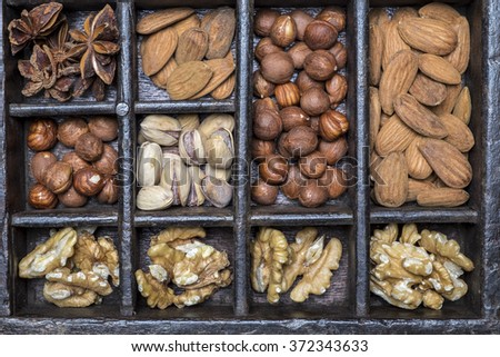 Almonds, walnuts, pistachios, anise and hazelnuts in wooden bowls on wooden background - stock photo
