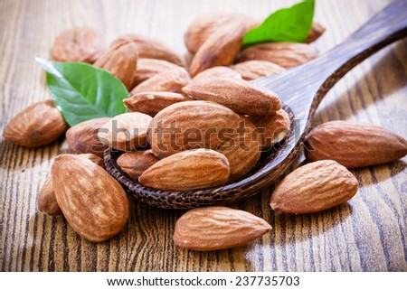Almonds with leaves isolated on wood background - stock photo