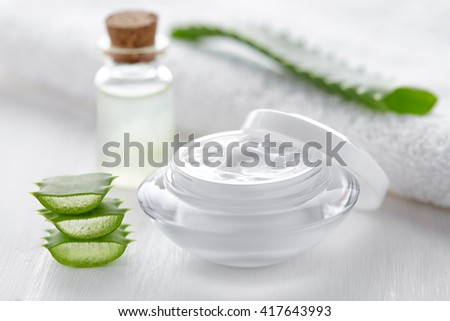 Aloe vera cosmetic cream face, skin and body care hygiene moisture lotion wellness therapy anti wrinkle mask in glass jar with towel on white background - stock photo