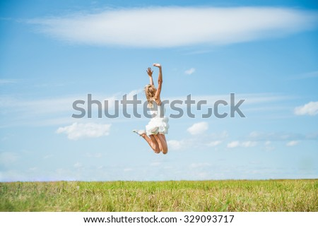 Alone blond Woman Jumping for Joy on a Grass Hill above horizon line One happy slim woman fly in a green field against blue summer sky with clouds  - stock photo