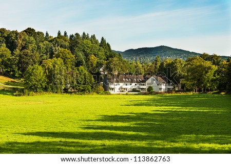 Alone farmhouse on a meadow in forrest - stock photo