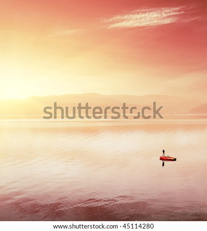 Alone fisherman in boat on huge lake under sunset light - stock photo