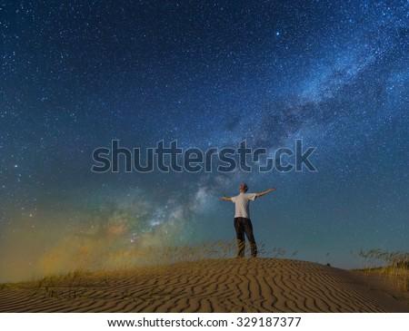 alone man under a night sky in a desert - stock photo