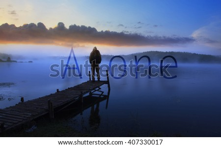 """alone man watching sunrise near lake, conceptual poster with word """"alone"""" added  - stock photo"""